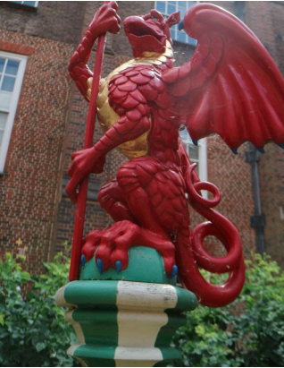 red dragon sitting on a pedestal holding a staff